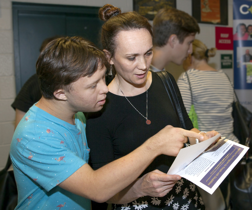A mom and son look at information at a Transitioning Youth fair.