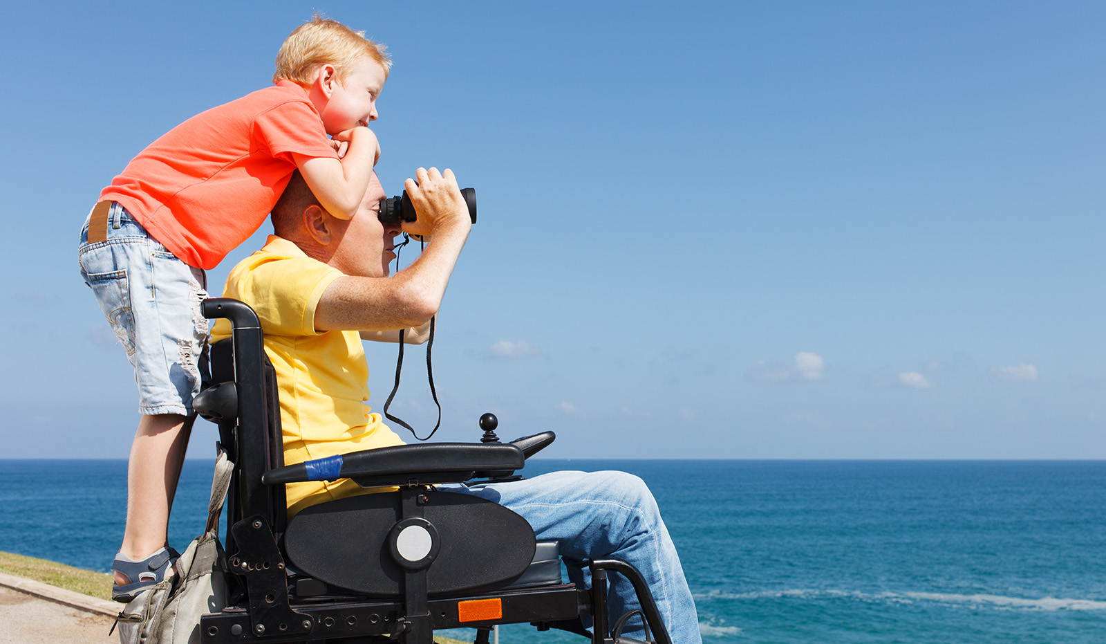 Disabled father looking through binoculars while his young boy is on the back of his wheelchair